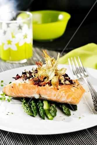 Salmon fillet with tomato oil on asparagus