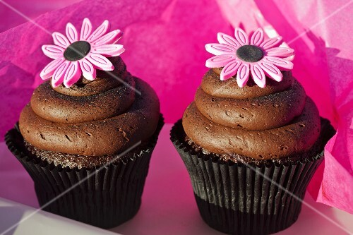 Chocolate cupcakes with caramel filling, chocolate icing and pink sugar flowers