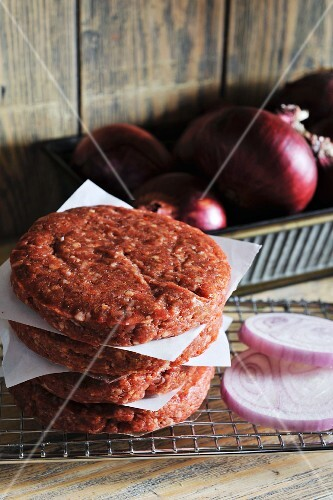 Raw burgers and sliced onions
