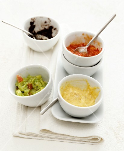 The remains of four different dips in small bowls