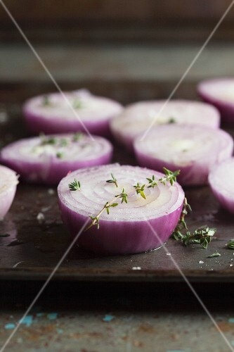 Red onions, in slices, for roasting on a baking tray (close-up)