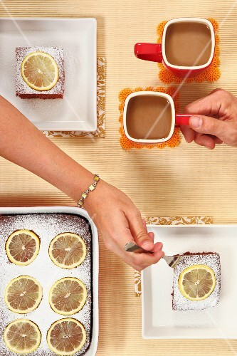 A woman having a slice of chocolate & lemon cake with a cup of coffee
