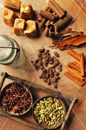 Assorted spices on a wooden table (cinnamon bark, cinnamon sticks, star anise, cardamom and palm sugar)
