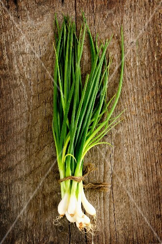 A bunch of spring onions on a wooden surface