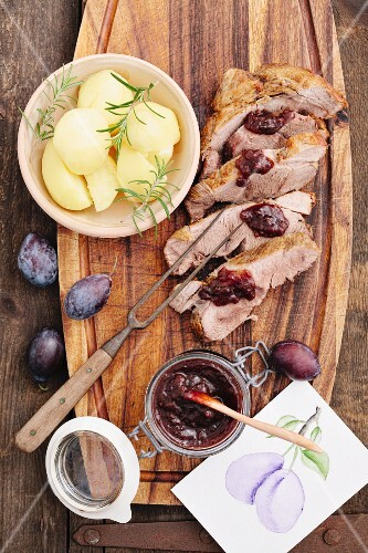 Roast pork, cut into slices, with plum chutney and boiled potatoes