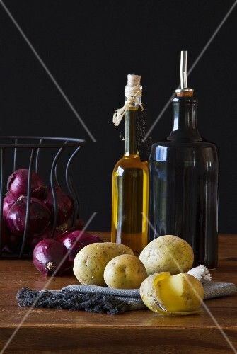 Still-life arrangement of red onions, potatoes, vinegar and oil
