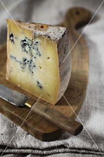 Gorgonzola with a knife on a wooden board