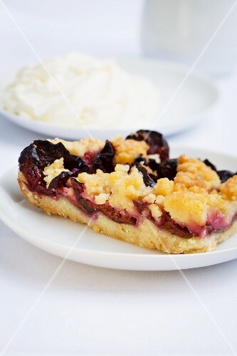 A slice of plum crumble cake with cream