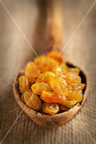 Closeup of golden raisins in an old wooden spoon