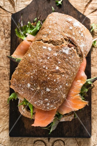 A smoked salmon and lettuce sandwich on a chopping board