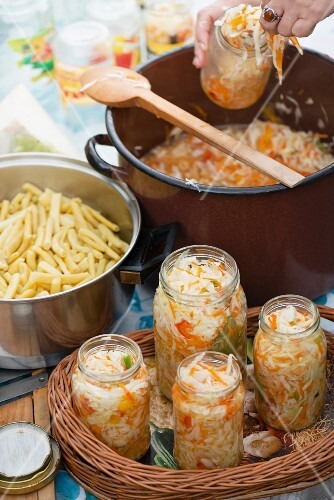 White cabbage and carrot salad with red peppers in jars