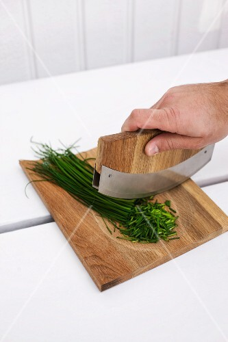 Chives being chopped with mezzaluna knife