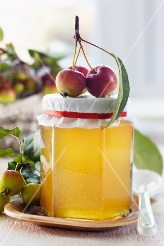 A jar of apple jelly decorated with ornamental apples
