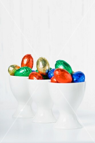 Colourful chocolate eggs in eggcups