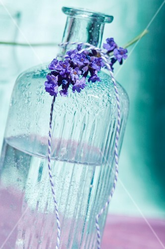 A bottle of scented oil and a sprig of lavender