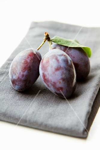 A bunch of three plums on a napkin