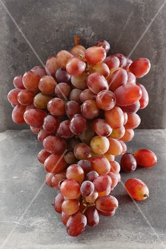 Pink grapes with a stone background