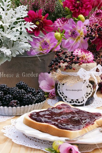 Toast with blackberry jam in front of a bouquet of summer flowers