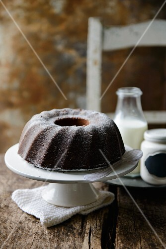 Bundt cake and a bottle of milk on a rustic wooden table