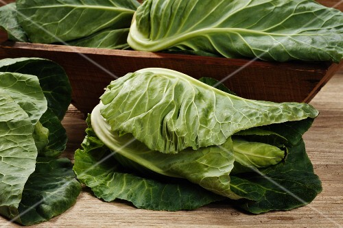Pointed cabbages, some in a wooden bowl