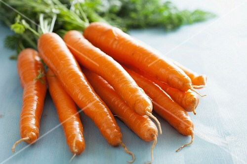 Fresh carrots on a pale blue surface (close-up)