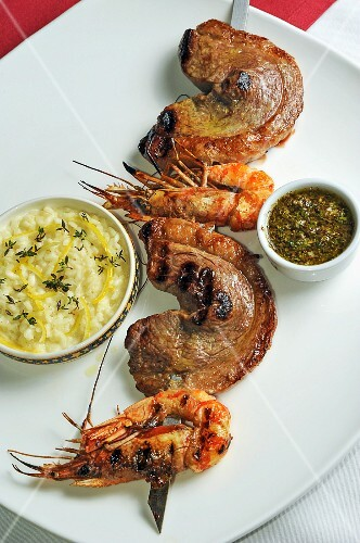 A skewer of barbecued beef and prawns, with lemon risotto