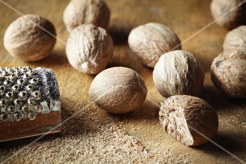 Nutmeg, whole and grated, with a nutmeg grater