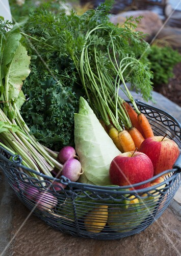 Assorted types of vegetables and apples in a wire basket