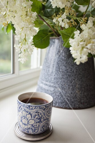 A mug of tea in front of a bunch of lilac flowers in a ceramic mug