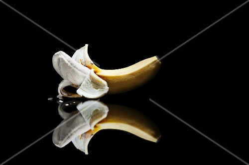 An artistically presented slightly peeled banana coated with liquid foundation make up