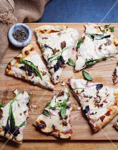 Homemade pizza with broccoli rabe, spinach, and fresh basil on a wooden board