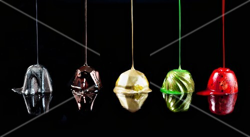 Chocolate truffles being drizzled with colors of nail polish