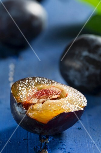 Plums, one halved, on a blue wooden tabletop