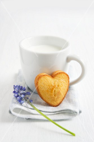 A cup of milk with a madeleine heart