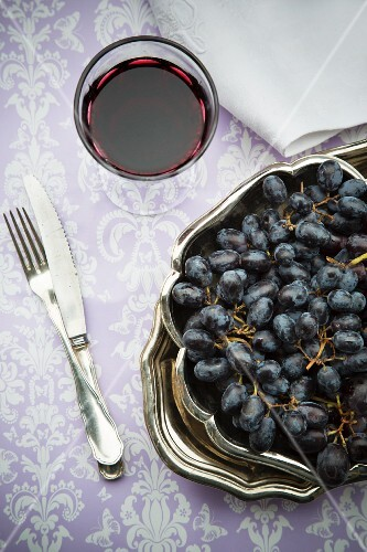 Red grapes, a glass of red wine, a napkin and silver cutlery