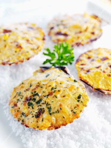 Scallops topped with cheese and parsley and baked in the shell