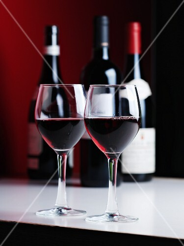 Two glasses of red wine in front of bottles of red wine