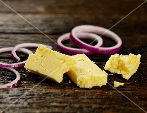 Cheddar and red onions on a wooden surface