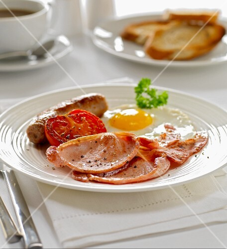 Bacon with fried egg, fried sausage and tomato, for breakfast