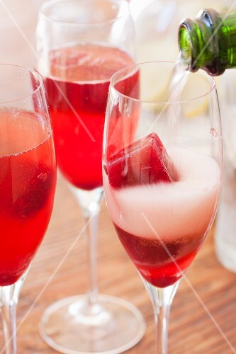 Pouring Champagne over frozen juice cubes
