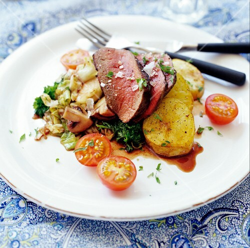 Beef steak with fried potatoes, tomatoes and mushrooms