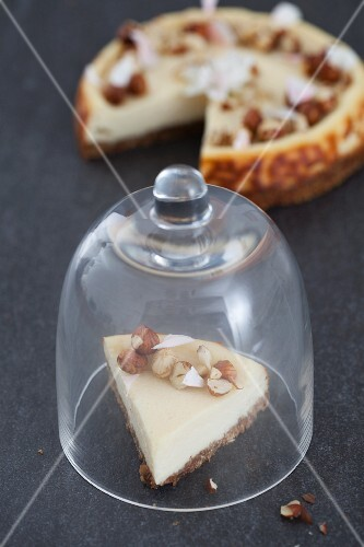A slice of vanilla cheesecake with smoked cream cheese and hazelnuts under a glass cloche