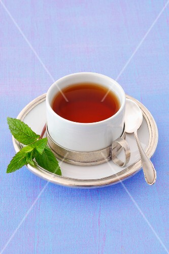 A cup of peppermint tea with a sprig of mint