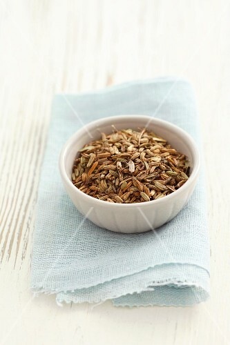 Aniseeds in a small bowl on a cloth