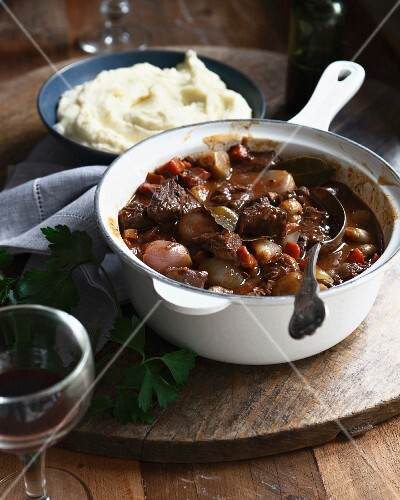 Beef daube in casserole dish with bowl of mashed potatoes