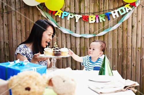 Mother showing cakes to baby boy