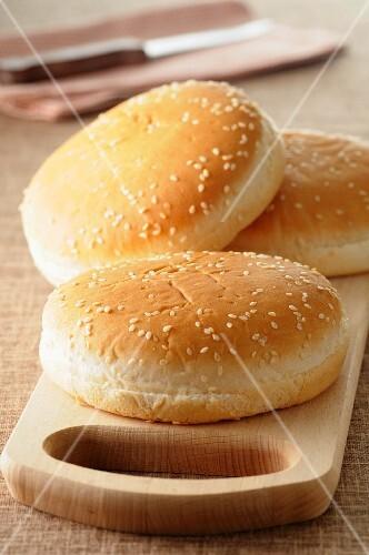 Three hamburger buns with sesame seeds