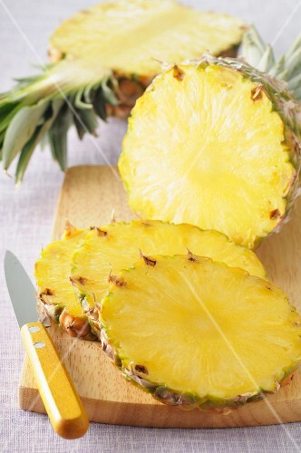 Pineapple, in slices and cut in half, on a chopping board