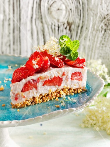 A slice of rhubarb and rice pudding tart with strawberries and elderflowers