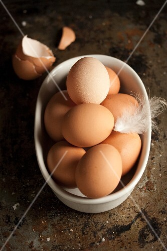 Fresh brown hen's eggs with a feather